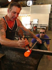Joe Hobbs, left, and Jacob Moody work on creating a glass pumpkin at First City Art Center.  Hobbs will present a Seconds Sale, featuring prototypes and imperfect pieces of hand-blown and sculpted glass at reduced prices, on Saturday.