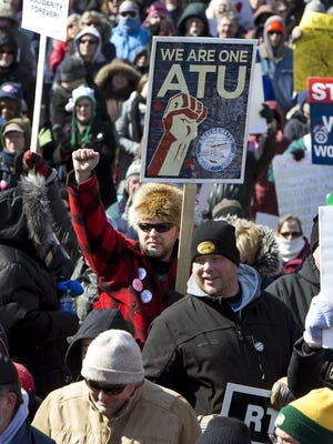 "Marc LeClair, of Wausau, Wis., center with sign, marches during a rally against a ""right-to-work"" proposal, on Saturday, Feb. 28, 2015, in Madison, Wis. Thousands of Wisconsin union workers rallied at the Capitol Saturday to protest a ""right-to-work"" proposal that would outlaw the mandatory payment of union dues, but the crowd was much smaller than those in 2011 against Gov. Scott Walker's law stripping public sector unions of much of their power."