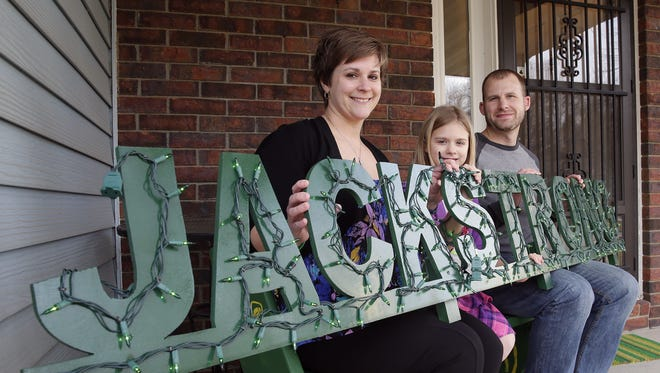 Renee, Ella and Jason Natzke hold a lighted sign at their Green Bay home Monday, March 21, 2016, that spells out #JackStrong in memory of their son and brother Jack, who died at age 5 six months ago.