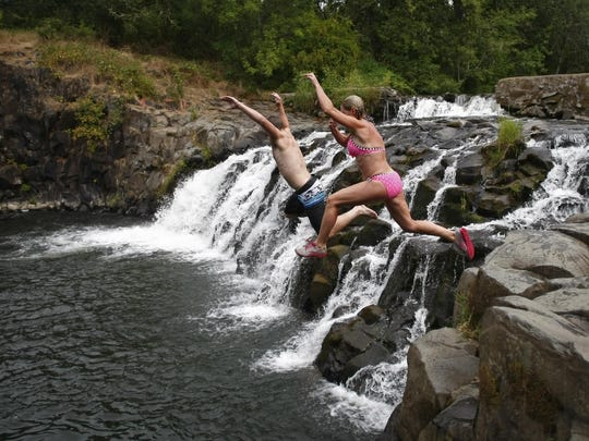 Top: Tammy Berks and son Sterling jump from the rocks to cool off in Butte Creek at Scotts Mills Park last summer.