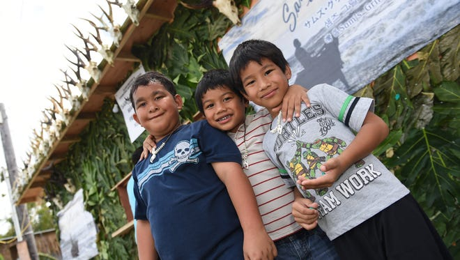 Sablan brothers Jude Paul, 7, left, Christopher Paul, 4, center, and Rudy Paul, 6, right, in front of the Sam's at the Bay food stand during Guam History and Chamorro Heritage Day in Umatac on Feb. 25, 2017.