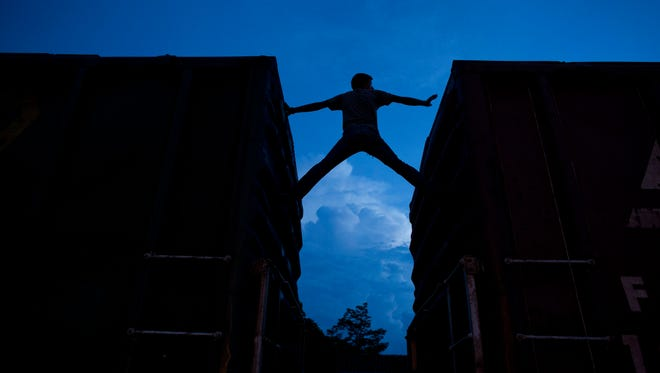 In this Thursday, June 19, 2014 photo, a Central American migrant practices scaling parked boxcars, as he awaits the arrival of a northbound freight train in Arriaga, Chiapas state, Mexico. The number of unaccompanied minors detained on the U.S. border has more than tripled since 2011. Children are also widely believed to be crossing with their parents in rising numbers, although the Obama administration has not released year-by-year figures.