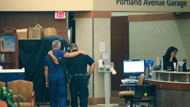 A member of the Rochester General Hospital medical staff and a Rochester police officer walk together down the hallway after a news conference early Thursday.