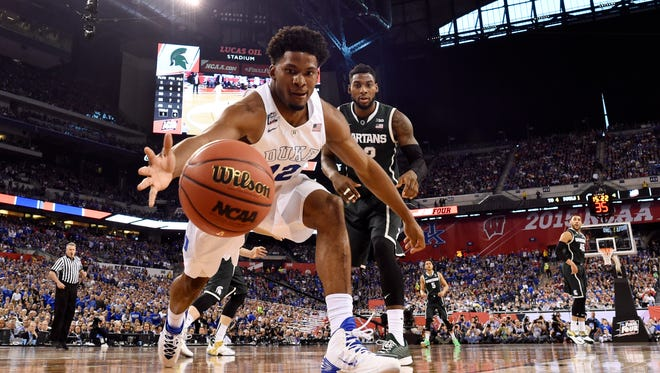 Duke Blue Devils forward Justise Winslow (12) dives to try to save a ball from going out of bounds as Michigan State Spartans guard/forward Branden Dawson (22) looks on in the second half of the 2015 NCAA Men's Division I Championship semi-final game at Lucas Oil Stadium.
