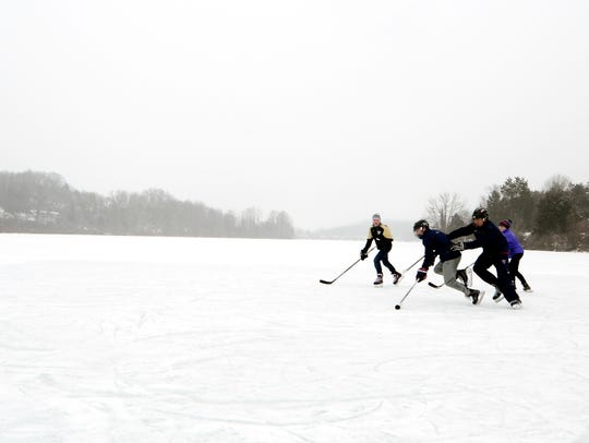 A group of teens play ice hockey on Lake Redman in
