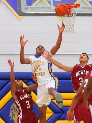 Newark juniors Khayle Woods and Darius Shackleford go up against Gahanna Lincoln's Nick Ward for a rebound Friday during the Wildcats' 55-53 victory for their 1,500th win.
