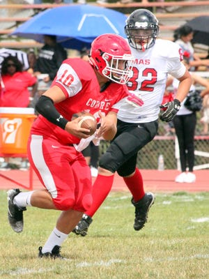 Cobre's Gilbert Soto looks for some running room against Mission Charter's defense Saturday afternoon. The Indians won, 48-0, to get their fiirst victory of the season.