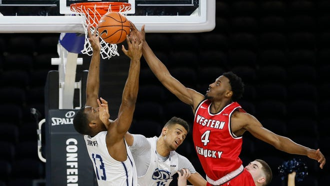 Western Kentucky Hilltoppers guard Josh Anderson (4) and Old Dominion Monarchs forward Aaron Carver (13) fight for a rebound during the second half during the Conference USA Tournament at Ford Center at The Star.