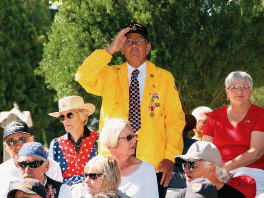 Bill Armendariz - Headlight Photo   US Army veteran Chuck Brandes stands at attention and salutes during the playing of the armed forces military songs at the Memorial Day ceremony on Monday hosted by the American Legion Bataan Post 4 at Mountain View Cemetery.