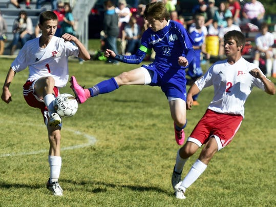 McConnellsburg defender Nick Culler (2) battles for the ball between Fannett-Metal's Layton Hoffman (1) and Levi Brady on Monday. The Spartans defeated F-M, 3-0.