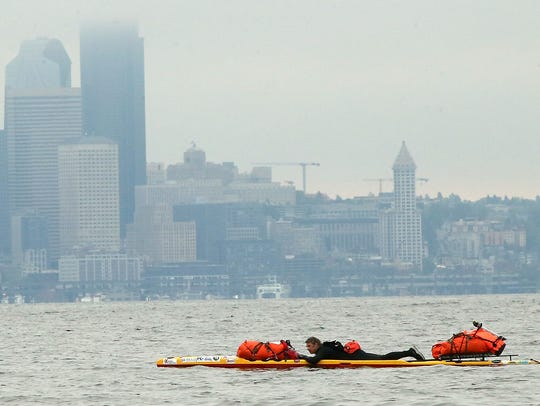 The Seattle skyline looms in the background as Steve Rhoades paddles along the shore of Bainbridge Island's Rockaway Beach on Tuesday. Rhoades will paddle from Bainbridge to Port Townsend to Ketchikan, Alaska this summer, all as a fundraiser for the homeless. Rhoades was once an addict and was himself homeless for 15 years but now runs an organization called Extreme Sobriety, which provides support and training for the homeless, addicts and others.