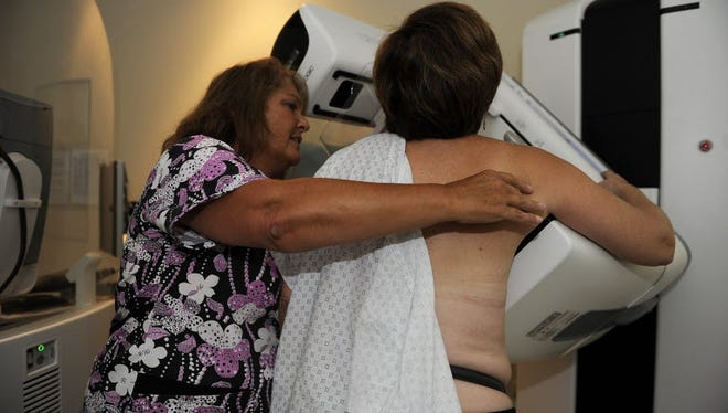 In this 2012 file photo, a woman is positioned by a technician for a 3-D mammogram screening called tomosynthesis at Washington Radiology Associates in Virginia.