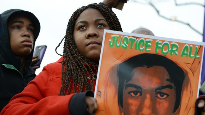 Tatianna Taylor holds a Trayvon Martin sign as the Rev. Al Sharpton speaks  during the National March Against Police Violence in Washington, D.C. in 2014.