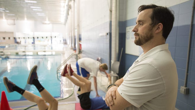 Fort Collins Area Swim Team (FAST) coach Chris Webb watches swimmers warmup for practice at EPIC on Wednesday. The connection between FAST and local high schools has helped turn Fort Collins into a dominant swim city.