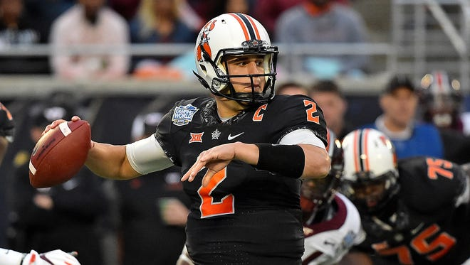 Oklahoma State Cowboys quarterback Mason Rudolph (2) attempts a pass against the Virginia Tech Hokies during the first half in the 2017 Camping World Bowl at Camping World Stadium.