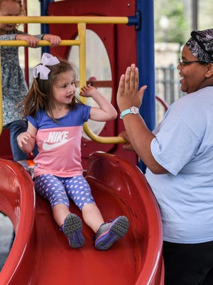 Anna Claire Cox, left, gives teacher Lydia Dandy a high-five at the Clemson United Methodist Church Little Lights Learning Center in Clemson on Tuesday.