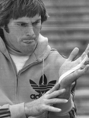 Bruce Jenner tests his injured finger before the start of the shot put when he competed in the decathlon at the 1976 Drake Relays.