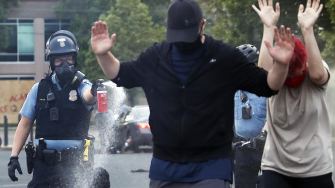 An officer points pepper spray towards people after curfew on Sunday, May 31, 2020 in Minneapolis. Protests continued following the death of George Floyd, who died after being restrained by Minneapolis police officers on Memorial Day.