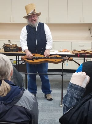 Mike Anderson, a Civil War-era music enthusiast, shows off one of his many instruments during a special program Saturday, March 25, at the Victor Public Library.