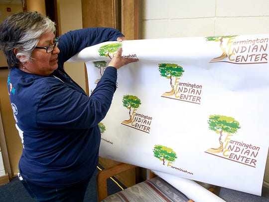Myra Newman, division manager for the Farmington Indian Center, shows the backdrop that will be used for photos of visitors to this weekend's song and dance program at the center.