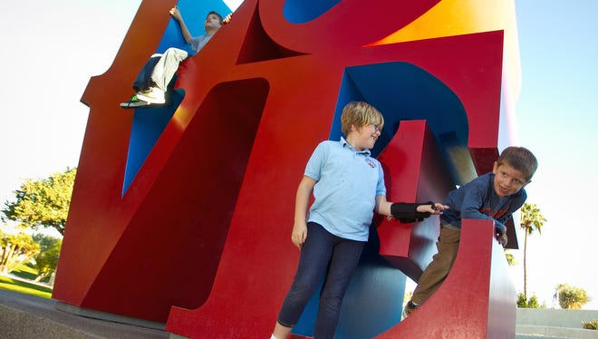 Kids play on the LOVE sculpture at Scottsdale Civic Center Mall.