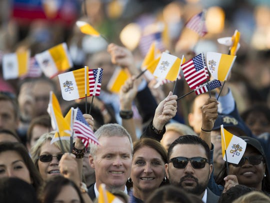 People wave flags as  President  Obama greets Pope