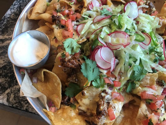 Nachos are smothered with beer cheese, brisket burnt