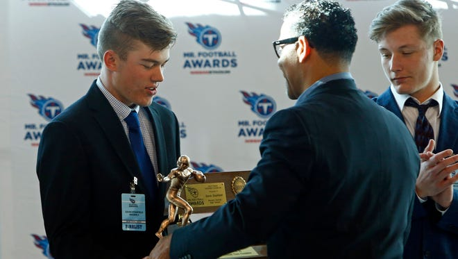 Waverly Central's Gavin Stanfield accepts his Mr. Football trophy from former Titans player Blaine Bishop in November at Nissan Stadium.
