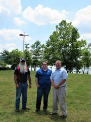 "Marty Roberts, Sarah Terry and Brad Brummett represent FUD employees who have ""adopted"" the two osprey pairs. The first nest they relocated is seen behind them."