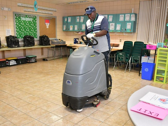 J.M. Brown, head custodian at Imperial Estates Elementary School in Titusville, cleans the floors before the school opens as a shelter for Hurricane Irma.