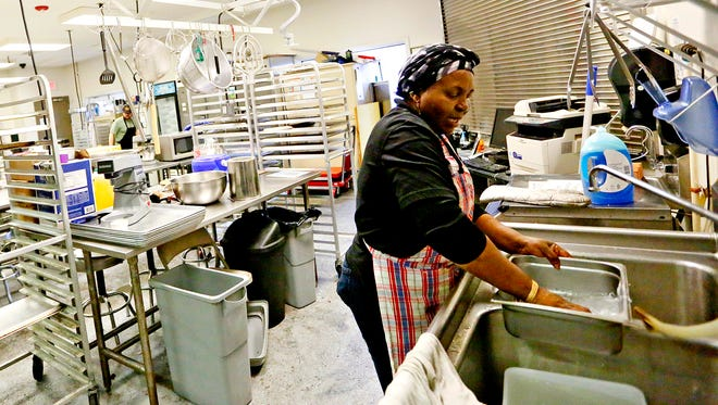 Amaa Achu, of Global Cafe, washes her dishes in YorKitchen while preparing food to be served in Central Market in York City, Thursday, Jan. 26, 2017. York County Economic Alliance has been operating YorKitchen in Central Market since 2011 but operations will be transferred to the market beginning in February. Dawn J. Sagert photo