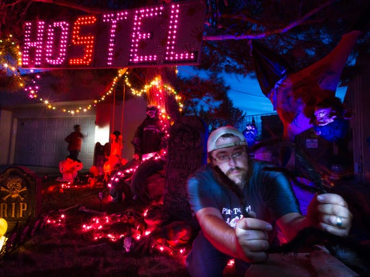 Devon Jones, of Las Cruces, right, decorates his home located off of Roadrunner Parkway for Halloween on Monday, October 24, 2016. Jones' birthday falls on October 30 -- he and his mother decorate both their homes, which are located side by side, for the occasion. The family started working on the decorations on October 1st.