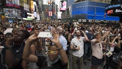 People in Times Square try to takes photos and view
