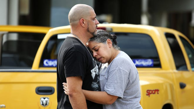Ray Rivera (left), a DJ at Pulse Orlando nightclub, is consoled by a friend after the June 12 mass shooting at the club.