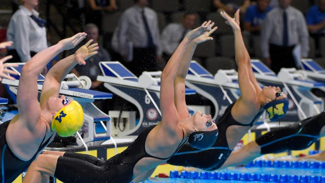 Clara Smiddy, from left, Amy Bilquist and Ali Deloof dive at the start of a women's 100-meter backstroke semifinal at the U.S. Olympic swimming trials, Monday, June 27, 2016, in Omaha, Neb.