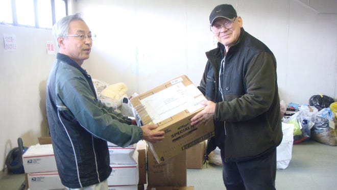 """In this photo provided by Joseph Roginski, taken May 13, 2011, Joseph Roginski, right, holds a package in a storeroom of the Misawa City Hall in Japan, where donations of clothing and supplies were being kept for earthquake relief efforts. He says that while the cost of living is higher in Japan, access to health care is not. """"Things are very expensive here. It is impossible to live off Social Security alone,"""" said Roginski, who was stationed in Japan in 1968. """"But health insurance is a major factor in staying here."""" The former military language and intelligence specialist said he pays $350 annually to be part of Japan's national health insurance. His policy covers 70 percent of his costs. The rest is covered by a secondary insurance program for retired military personnel."""