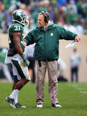 Michigan State Spartans head coach Mark Dantonio talks to cornerback Darqueze Dennard during a game against Purdue. The Spartans' strong defense will be put to the test against Michigan.