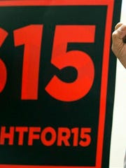 A supporter of a $15 minimum wage holds his fist in