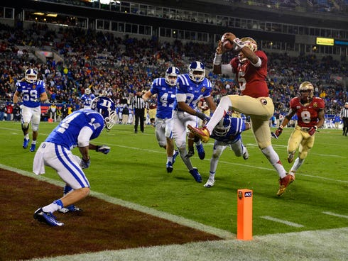 Florida State quarterback Jameis Winston leaps into the end zone for a third-quarter touchdown in the Seminoles' rout.