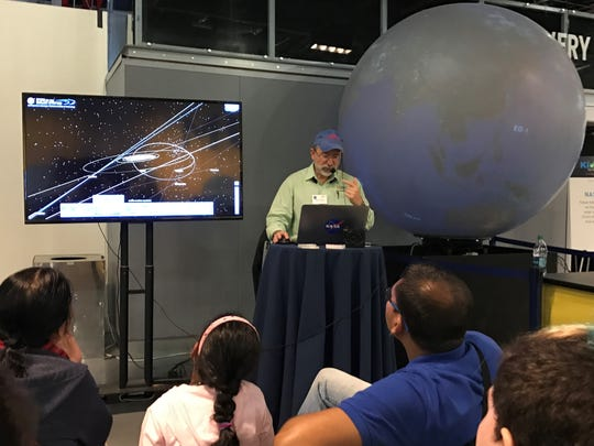 Kevin Hussey a manager within NASA's Jet Propulsion Laboratory demonstrates to  youngsters and their parents how a software called Nasa's Eyes works.