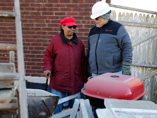 Tammy Tooles, wife of Elijah Tooles, a WWII veteran, talks with Karl Williams, of Easterseals, Operation Vets THRIVE, as a dilapidated garage was removed from her home Thursday December 29, 2016. The City of Cincinnati had threatened the Tooles with fines, if they didn't take down the garage in their back yard. The Easterseals Operation Vets THRIVE program which helps about 700 Veterans per year in the areas of emergency assistance, employment, & education, coordinated the effort to remove the shed and other debris from the yard at no cost.