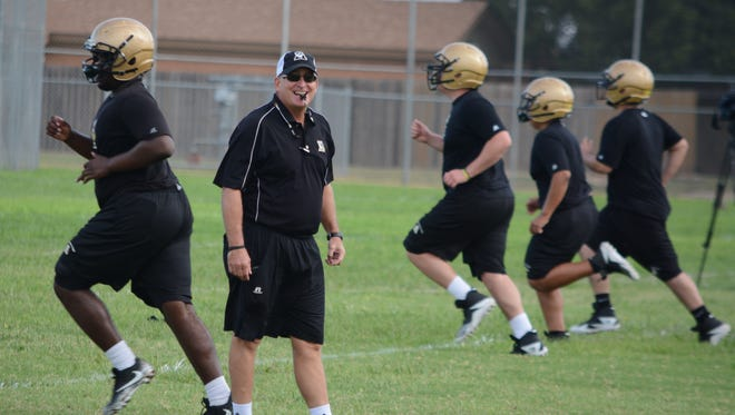 Abilene High football coach Del Van Cox laughs with his assistant coaches during conditioning drills at the Eagles' first fall practice Monday morning at AHS' on-campus practice fields.