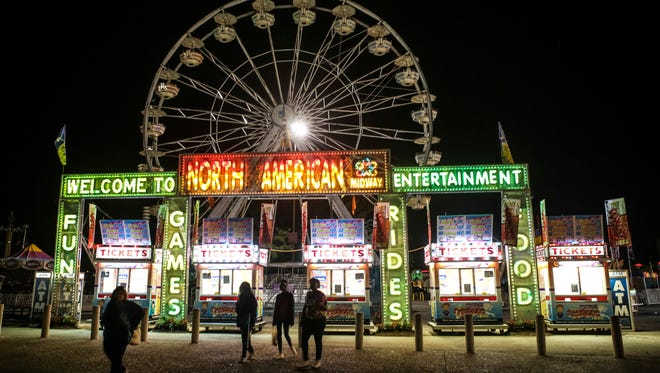 Attendants file out of the Kentucky State Fair at closing time Monday evening. Aug. 24, 2015