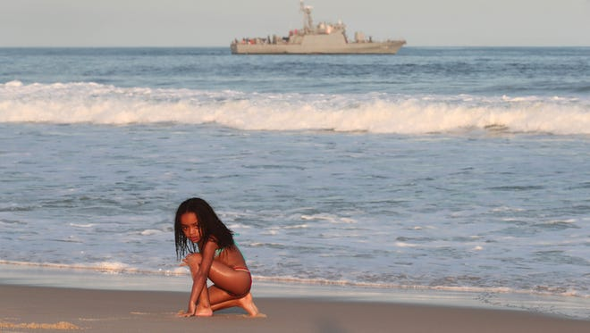 A young girl plays in the sand as a Brazilian navy warship patrols off-shore at Copacabana Beach prior to the start of the Rio 2016 Olympic Games.
