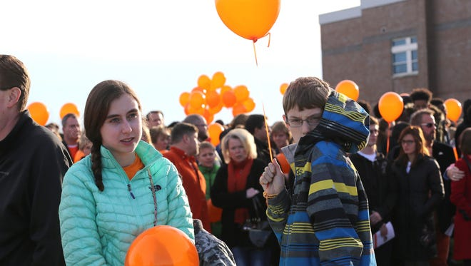 Emily Schwartz,14, and her brother Russell Schwartz, 11, of Plymouth hold balloons in the cold before releasing them in front of Saline High School Performing Arts Center in honor of Charles (Chad) Clinton Carr.