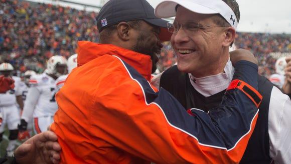 Auburn head coach Gus Malzahn, right, embraces wide-receivers