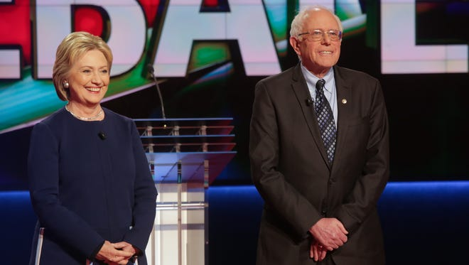Democratic Presidential candidates Hillary Clinton and Bernie Sanders stand on stage before the start of a debate in March.