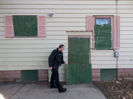 Milwaukee Police officer Kevin Vodicka checks the condition of a boarded-up house Friday, March 16, 2018 check out a complaint from neighbors near S. 26th St. and Greenfield Ave. in Milwaukee, Wis. Since 2000, the Milwaukee County district attorney's office has stationed prosecutors in city neighborhoods. Lopez works in tandem with a police officer and a community organizer. The teams focus on blight and take action designed to improve quality of life, such as shutting down drug houses, holding absentee landlords accountable and making sure taverns follow the rules. At its height, there were seven Community Prosecution Units, one in each police district. Now, there are three.