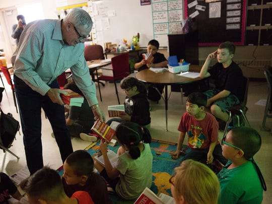 Dave Wright, with the Rio Grande Rotary Club, hands out dictionaries to third-graders at Sunrise Elementary School, Tuesday, March 28, 2017.
