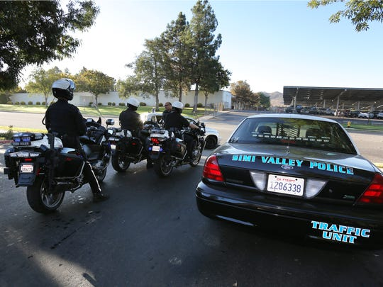 Police Cmdr. Robert Arabian, standing in front of motorcycles, talks to officer Eric Bowman, from left, officer Chris Coulter and Sgt. Billy Lappin after monitoring speed in front of Simi Valley High School and giving out citations to speeding motorists.